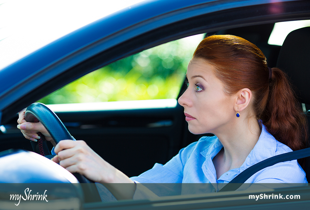 A woman driving trying to keep her eyes open because she's suffering from highway hypnosis.