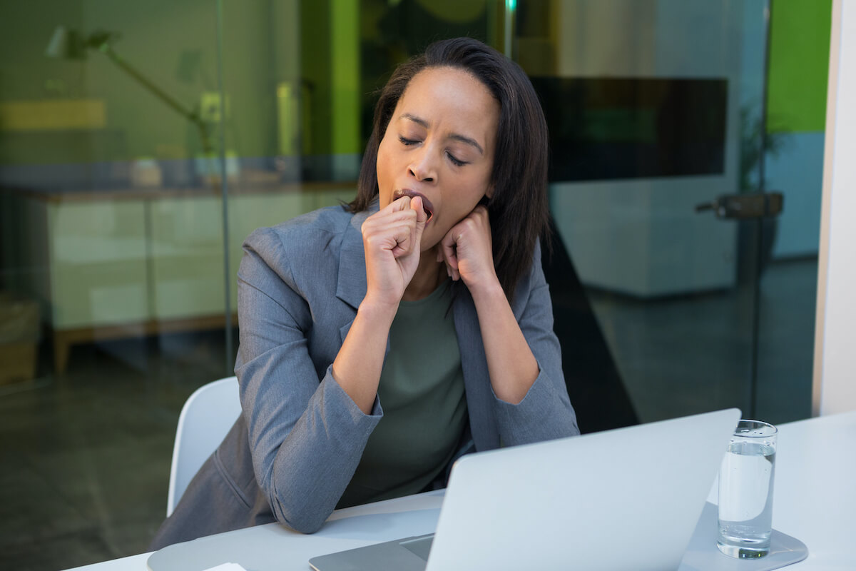 a business woman sitting at a computer is not having a problem in yawning completely